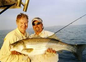 "Walter Manley in 2008 with a 28 pound striper (held by Richie Gaines) caught in the Chesapeake on a trip with SAE fraternity brothers. Shortly after, Walter caught the record 49 pounder that year and needed all of his 6'3"" height and 215 pounds to bring the fish to the boat."